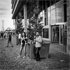 "Snacking in front of ""De Rotterdam"" Building (John Riper) Tags: johnriper street photography straatfotografie square vierkant bw black white zwartwit mono monochrome netherlands candid john riper canon rotterdam marine port worldportdays wereldhavendagen 6d 24105 woman man eye contact snacking lunch eating people"