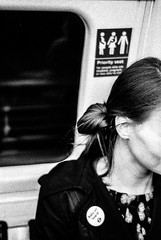 London Street: Baby on Board (christait) Tags: street uk woman london underground pin britain tube pregnant transit ilforddelta3200 priorityseating babyonboard leicam3 ilfotechc zorky50mmf2jupiter8