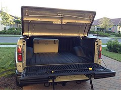 A Black Truck Bed cover on a Ford Raptor (DiamondBack Truck Covers) Tags: ford se aluminum open c pickuptruck driveway raptor rearview diamondback diamondplate whitetruck ff09 tonneaucover truckbedcover tailgatedown onepanelopen ruggedblack