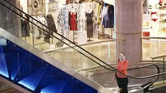 Woman talking on the phone in shopping centre. (greycoastmedia) Tags: woman motion girl up mobile mall shopping video phone telephone escalator young cell talk shoppingcentre communication upstairs speak communicate footage movingstaircase movingstairway stockvideo greycoastmedia
