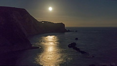 as the moon rises over Dorset's Jurassic Coast (lunaryuna) Tags: dorset jurassiccoast durdledoor lulworth night nightshot nightphotography nocturnalphotography moon moonrising reflection sea cliffs bluff landscape lunaryuna