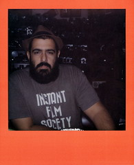The King In His Castle (tobysx70) Tags: the impossible project tip polaroid slr680 frankenroid sx70 door rollers color film for 600 type cameras colorframesedition frames edition orange impossaroid thekinginhiscastle denton camera exchange piner street texas tx armand beard man owner portrait instantfilmsociety tshirt hat polacon2016 polaconone 100216 toby hancock photography