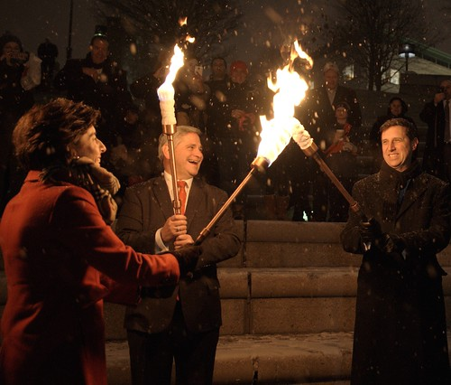 Governor Gina Raimondo passes the flame to Lt. Governor Dan Mckee and General Treasurer Seth Magaziner during the WaterFire Lighting Ceremony. Photo by John Nickerson.