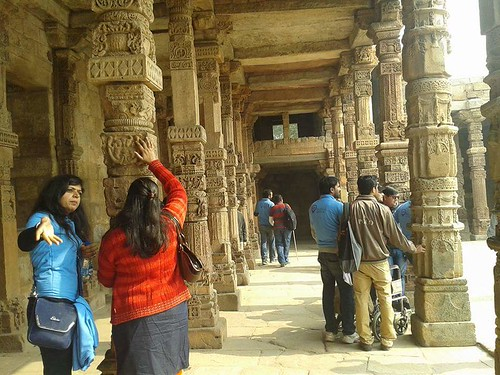 Accessible Tour of Qutub Minar: One of travel buddy interacting with a traveller with disability.