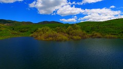Devil's Creek Reservoir 12 (Dan Beland) Tags: sky usa mountain lake art beach nature water reflections landscape unmodified spring unitedstates artistic outdoor bluewater bluesky reservoir hills idaho snowcapped shore northamerica rockymountains verdant serene ripples idyllic rollinghills springtime unedited drone snowcappedmountains yellowwildflowers fluffywhiteclouds nofilters perfectweather noadjustments dji straightoffthecamera lushgreengrass quadcopter devilscreekreservoir phantom3professional bannockidaho