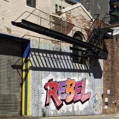 Rebel on 26th Street (Joel Raskin) Tags: graffiti rebel fireescape shadows nyc chelsea manhattan streetart brickwall square 11