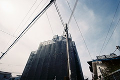 suburbia japonica: cloaked (troutfactory) Tags: building construction sheathing cloaked wrapped powerlines 豊中市 toyonaka 大阪 osaka 関西 kansai 日本 japan voigtlanderbessal 15mheliar wideangle analogue film kodakgold400