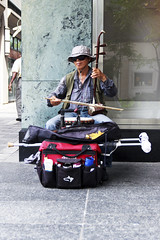 Traditional Two-String Melody (Ben Aerssen) Tags: erhu streetperformer sidewalk city street wall window man elderly bow strings backpack crutch hat sunglasses shirt outdoors traditions traditional twostringed violin chinese grey gray beige black red blue green teal brown fiddle sitting smirk