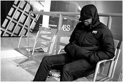 Carelessly dying (mesonparticle) Tags: sleeping england blackandwhite bw man london chair waiting sitting bored streetphotography waterloo tired resting waterloostation londonwaterloo x100t topgunning