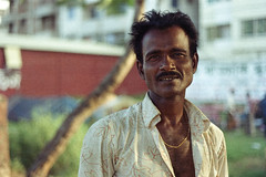 The Man With the Gold Chain (Sheikh Shahriar Ahmed) Tags: street light portrait man film analog gold jewellery chain fujifilm konica dhaka bangladesh banasree hexanon moustach 50mmf17 hexanon50mmf17 fujicolorc200 dhakadivision konicaautoreflext3n sheikhshahriarahmed