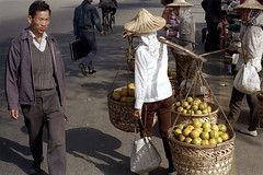 32-397 (ndpa / s. lundeen, archivist) Tags: nick dewolf nickdewolf 32 reel32 color photographbynickdewolf 1970s 1972 fall film 35mm winter republicofchina taiwan taiwanese city citylife candid streetphotography streetlife people man woman women onfoot pedestrians basket baskets fruit produce hat hats conicalhat conicalhats yoke shoulderyoke carry carrying bag bags bike bicycle china chinese shoulderpole carryingpole