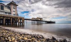 Pier (absynth100) Tags: seashore sea pier rocks water building reflections sky clouds wales penarth pebbles seascape coast blue