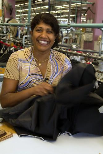 Female Factory Worker Holding Garment / Travailleuse en usine tenant un vêtement