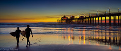 Heading In (Greg Adams Photography) Tags: ocean california sunset sea people water silhouette reflections pier waves pacific dusk silhouettes shore wharf surfers southerncalifornia huntingtonbeach hhsc2000