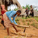 Young Women Chopping Wood as Children Play in The Background, Malawi