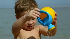 Little boy having fun with toy waterpot (greycoastmedia) Tags: ocean boy sea summer vacation motion game beach water childhood fun toy video seaside kid child play little outdoor leisure pour playful waterpot footage wateringpot stockvideo greycoastmedia