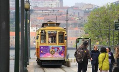 The historical tram is a splendid way to discover Porto (Bn) Tags: rua31dejaneiro igrejadosclrigos yellowbus churchofsaintildefonsoigrejaparoquialdesantoildefonso city street porto oporto arteaosmolhos alley raining day rain tower architectural heritage portugal bell church strolling up climbing climb capital douro river cluttered cobbled ascending decending local markets facades harbor tourism tourist walking port wines unpretentious urban faades ambience old history characteristic symbols unesco world travel monastery sdoporto cathedral roman catholic cloister walk gallery decorations wisdom pontelusi luizi bridge luiz electric tram domlusibridge metrodoporto rainy umbrella sandeman fog 50faves topf50
