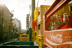 Revisiting Tsukiji empties (Eric Flexyourhead) Tags: street city red urban sun detail sunshine yellow japan tokyo bottles bokeh empty plastic drinks tsukiji   cocacola kirin recycling empties beverages ricohgr  chuo crates containers fragment shallowdepthoffield chuoku