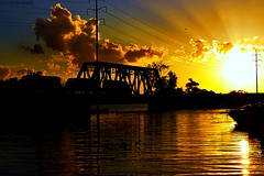 Train crossing Silver bridge on Cayuga lake at sunset (J and A's Photography) Tags: new trestle bridge sunset sky usa sun lake newyork nature water clouds train colorful state rays cayuga nysland