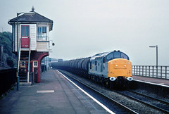And sadly dismal wever greets an ex-works tractor...growling thru Dawlish.... The box had been out of commision for some time and has now gone....6C30 37220 23-35 Waterston-Heathfield Dawlish station  Aug 1990 (the.chair) Tags: 6c30 37220 waterstonheathfield tanks dawlish station aug 1990