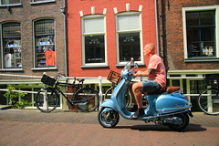 Blue Vespa (alideniese) Tags: man scooter vespa blue buildings street red paving bicycles streetphotography delft thenetherlands southholland daytime outdoors