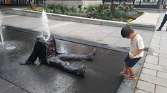 Headless Man in Fountain | Square Victoria, Montreal (Exile on Ontario St) Tags: montral fountain decapitated headless disembodiedhead body montreal fontaine water publicart installation silly surprising eau publique jetwater jet jets waterjet jetdeau jetsdeau squarevictoria quartier international district placevictoria shocking victoriasquare place square victoria urban urbain ville city vieuxmontral oldmontreal summer t person human clothes art public artpublic sitting drenched mouill wet tremp soaked soak vtements linge dcapit sans tte missing drench disembodied corps tronc squirting squirt sprinkler neck cou tranch coupe tt chopped kid child enfant glasses