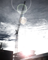 Bright Lights and Filigree (Steve Taylor (Photography)) Tags: city pink blue winter newzealand christchurch sky cloud sun white building green art texture sunshine metal digital sunrise circle dawn construction glare bright crane steel canterbury ring nz round flare southisland cbd tall