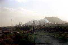 32-462 (ndpa / s. lundeen, archivist) Tags: nick dewolf nickdewolf 32 reel32 color photographbynickdewolf 1970s 1972 fall film 35mm winter republicofchina taiwan taiwanese kaohsiung kaohsiungcity city landscape mountain hill refinery oilrefinery smokestacks utilitypoles powerlines china chinese stanchions 1973