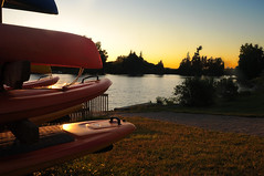 Stacked up for the Night (Poocher7) Tags: sunset summer orange ontario canada grass silhouette river outdoors evening dock pretty quiet dusk path peaceful cottagecountry serene lovely kayaks stackedup paddleboards