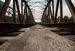 An old timer (modestmoze) Tags: bridge architecture nature plank wood wooden metal constructions 2016 500px outside outdoors shadows rusty rust traintracks tracks sky clouds white blue grey summer july lines old day green trees cracks