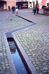 The rift (Nekr0n) Tags: street leica city 2 people urban color colour reflection slr film water 35mm vintage germany ed deutschland 50mm nikon wasser leute kodak pavement strasse grain streetphotography ishootfilm nostalgia summicron negative r stadt streetphoto 100 f2 135 5000 50 freiburg baden altstadt coolscan manualfocus v2 e55 ektar r5 mnsterplatz leitz bchle analoge primelens strase filmisnotdead munsterplatz summicronr kodakektar bachle leicasummicronr50mmf2e55 kodakektar100 imbreisgau