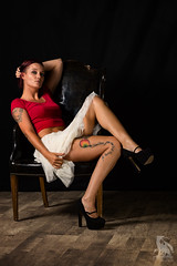 Kicked Back (CJ Schmit) Tags: wwwcjschmitcom 5dmarkiii canon canon5dmarkiii cjschmit cjschmitphotography canonef85mmf18usm photographermilwaukee milwaukeephotographer photographerwisconsin dragonspitstudios wauwatosa milwaukee wisconsin studio studioshoot modelshoot femalemodel nikkiwruk woman legs skirt croptop barefeet tattoos ink piercings woodfloor chair sitting heels red white shorthair portrait leatherchair pose thighs stomach sexy lady