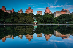 Conservatory Water (Amar Raavi) Tags: park nyc newyorkcity longexposure travel sunset usa ny newyork reflection clouds buildings evening pond unitedstates dusk centralpark manhattan scenic bluesky uptown uppereastside reflectionpond nycparks conservatorywater modelboatpond