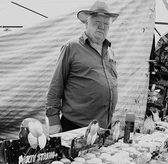 Smiler (Martyn61) Tags: street people blackandwhite bw man monochrome smile rural toys photography market outdoor stripes stall social fujifilm cowboyhat grumpy seller showground wcfields partyman partystring x100t ishouldshootraw