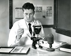 Studying a slide (PUC Special Collections) Tags: laboratory lab microscope pacificunioncollege chemistrydepartment chemistrylab chemistry beakers test tubes scientist labcoat experiments angwin california adventist sda seventhdayadventist college