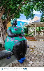 Big Mama sculpture by local artist Hortence Brouwn is located under a tree in Pietermaai District. (Vincent Demers - vincentphoto.com) Tags: abcislands amriquedusud antilles antillesnerlandaises architecture architecturecoloniale art artinstallation artist artiste artistelocal bigmama building btiment carabes caribbean caribbeanisland colonialarchitecture colorful color colourful curacao curaao destinationdevoyage destinationtouristique dutchcaribbean dutchcaribbeanisland espacepublic historicpietermaaidistrict home hortencebrouwn house iledescarabes installationpublique kingdomofthenetherlands localartist maison multicolore neighborhood netherlandsantilles photodevoyage photographiedevoyage pietermaai pietermaaidistrict publicart publicsquare quartier quartierpietermaai royaumedespaysbas sculpture southamerica streetart tourism tourisme travel traveldestination travellocation travelphoto travelphotography trip voyage willemstad cw
