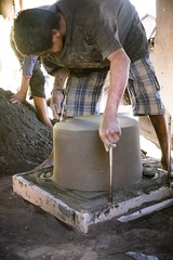 Hand shaping the cooking pot form out of volcanic sand.