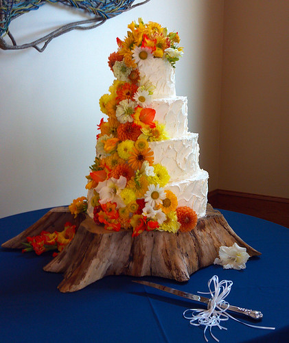 """A buttercream wedding cake covered in a cascade of yellow and orange fresh flowers. • <a style=""""font-size:0.8em;"""" href=""""http://www.flickr.com/photos/50891271@N03/16161214178/"""" target=""""_blank"""">View on Flickr</a>"""