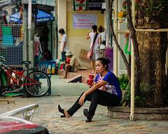 Woman On Khao San (Sound Quality) Tags: street travel blue portrait feet tourism canon thailand asia southeastasia highheels break drink bangkok candid streetphotography 711 breaktime efs1785mm uncomfortableshoes canon50d michaelwashington spirit7628yahoocom httpwwwflickrcomphotosmichaelwashingtonphotography