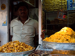 Chips seller (Evgeni Zotov) Tags: city portrait people food india man yellow shop market kerala banana chips snack indie sell indië trade merchant indien seller trivandrum inde trader shopkeeper インド hindistan 印度 भारत índia thiruvananthapuram הודו 인도 الهند индия