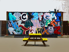 The Picnic Table (Steve Taylor (Photography)) Tags: art digital graffiti mural streetart bench table seat fence chainlink yellow white wood wooden newzealand nz southisland canterbury christchurch cbd city mall restart container abc letters alphabet picnic