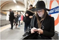 Lady in Black (mesonparticle) Tags: street england woman color colour london girl hat station mobile lady underground fuji phone platform streetphotography cellphone mobilephone headphones coventgarden fujifilm londonunderground thetube iphone appleiphone classicchrome x100t