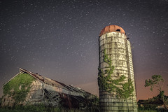 What Befell the Stars, so too the World of Man (reflectioninapool) Tags: westvirginia abandoned architecture astrophotography barn country dark fallen farm green growth horizontal landscape longexposure nature night outdoors purple rectangle ruins silo sky startrails stars trees vines