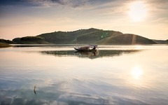 Peaceful on the lake (Asian Hideaways Photography) Tags: asia ambiance exterior reflection travel travelphotography sky sunset vietnam southeastasia landscape lake water sun boat hill thacba
