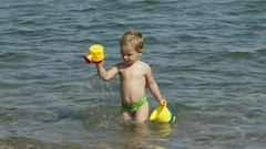 Adorable little boy playing in the sea (greycoastmedia) Tags: ocean travel family boy sea summer vacation people baby sun playing motion cute beach nature water beautiful childhood children fun toy outside happy person one freedom coast video kid bucket sand child play little joy young lifestyle happiness resort tropical leisure summertime 12 cheerful dig wateringcan swimwear footage caucasian wateringpot stockvideo greycoastmedia