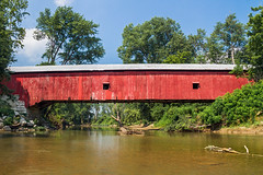 Putnam County Covered Bridge (Kenneth Keifer) Tags: road wood old bridge blue trees windows red sky usa reflection nature water clouds rural america creek vintage river landscape countryside wooden midwest colorful stream crossing vibrant rustic scenic vivid indiana sunny historic nostalgia covered transportation coveredbridge span greencastle oldfashioned roadway yesteryear putnamcounty bigwalnutcreek oakalla