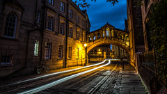 The bridge of sighs - Oxford, United Kingdom - Travel photography (Giuseppe Milo (www.pixael.com)) Tags: oxfordshire historic unitedkingdom ultrawide monument city greatbritain orange uk photography fuji sky yellow geotagged photo fujix harrypotter longexposure fuji14mm fuji14 bike sighs fujifilm light oxford fujixe2 bridge urban architecture ray motion car history clouds sun dusk europe xe2 travel onsale england landscape