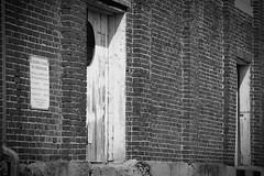Factory (Kendall Seitz) Tags: blackandwhite film 35mm arcitechture abandonded factory building wood door brick bw weathered barn sign old pattern contrast