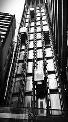 Great glass elevators (35mmMan) Tags: cameraphone city urban london glass monochrome architecture vanishingpoint blackwhite lift steel elevator perspective metropolis android lloyds samsungkzoom