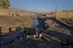 Children walking past garbage 9939 (shahidul001) Tags: poor indigent poverty deprived destitute child children kid kids boy boys girl girls canal sewercanal water garbage rubbish garbagedump pakistani pakistanis horizontal color colour day daylight quetta pakistan southasia asia drik drikimages